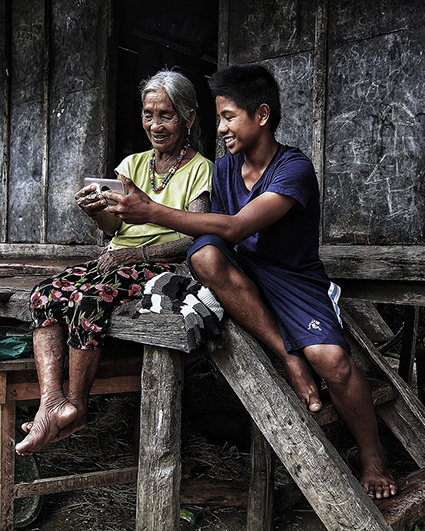 Family uses mobile phone in Philippine village